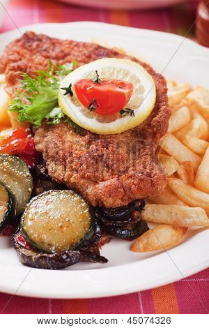 Viener schnitzel, breaded steak with french fries and vegetables