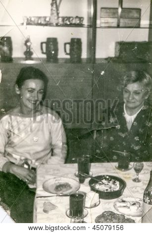 Vintage photo of aunt and adult niece during a family party, seventies