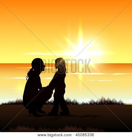 Silhouette of a mom with her child at seaside on evening background.