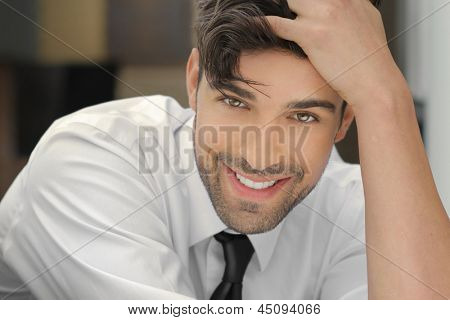 Handsome young man leaning on his hand with nice big real smile