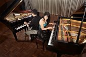 Two people, a couple playing duet musical performance with two grand pianos poster