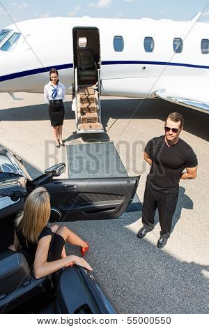 Woman stepping out of car parked by bodyguard; airhostess and private jet