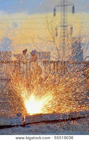 worker cut metal using blowtorch inside of plant