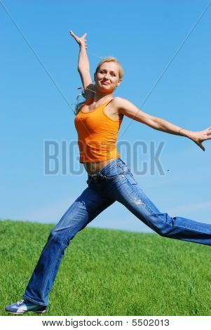 Happy Young Beautiful Woman Jump On The Meadow