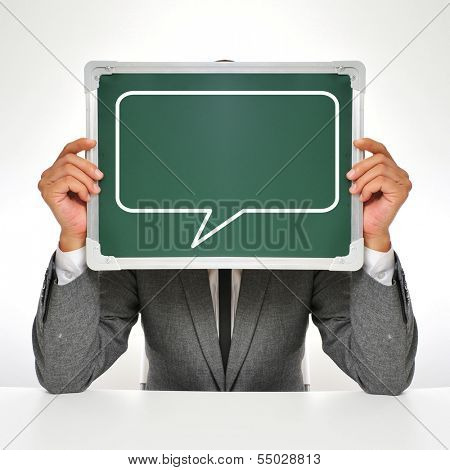 man wearing a suit sitting in a table holding a chalkboard in front of his face with a speech balloon drawn in it
