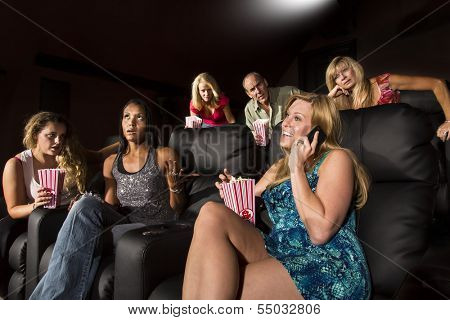 A woman on the phone with a group of people watching a movie showing emotion