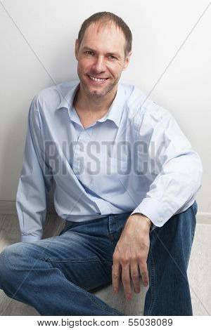 Portrait Of Smiling Man Sitting On The Floor