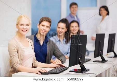 education, techology and internet concept - group of smiling students with computer monitor at school