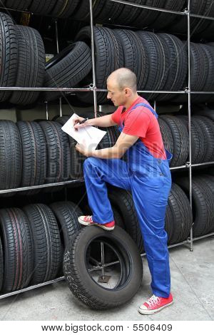 A worker takes inventory in a tire workshop and checks the stock. poster