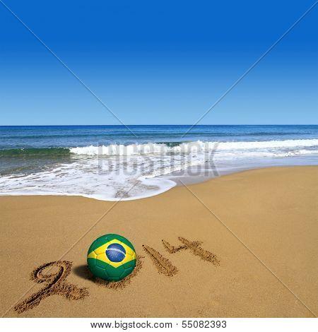 Soccer ball with Brazilian flag and 2014 on beach
