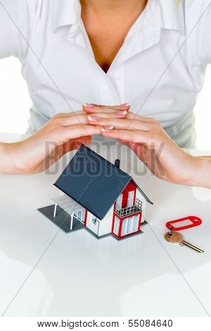 house is protected. woman holding hands over a model house