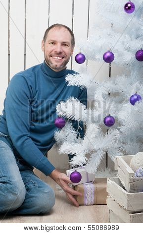 Smiling Man In Blue Near A Christmas Tree