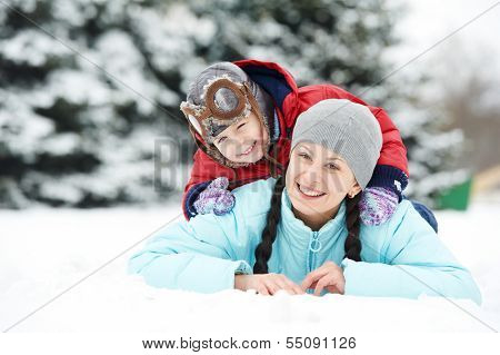 Portrait of happy mother with little child son boy and in winter outdoors
