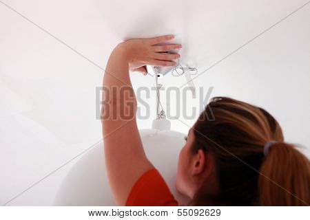handywoman fixing lamp