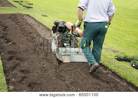 Man Rototilling The Ground