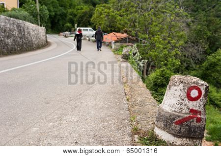 Couple Passing A Round Marker On A Descending Road