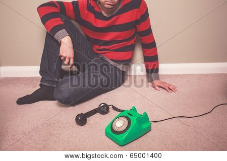 A young man is sitting on the floor and is desperately waiting for a phone call poster