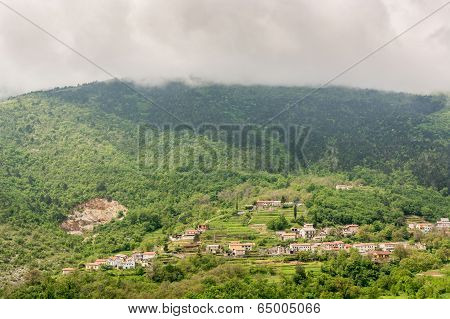 A Town Surrounded With Forest On A Mountain Slope