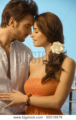 Young attractive casual caucasian couple having a romantic holiday moment at the seaside. Standing, eyes closed, touching, love, romance, flower in hair.