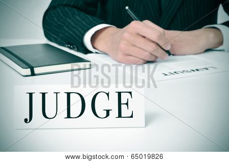 a man wearing in his desk with a nameplate in front of him with the word judge written in it