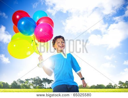 Cheerful boy outdoors holding balloons.