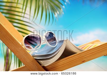 Summer holiday setting with book on beach chair