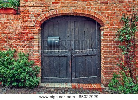 Old wooden door and red brick wall of rural house in Italy.