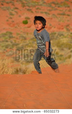 navajo children playing in the sand of monument valley