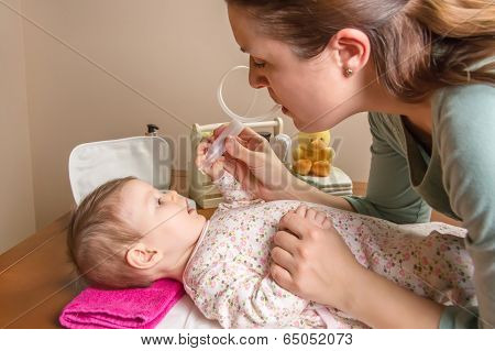 Mother cleaning mucus catarrh of adorable baby with a nasal aspirator poster