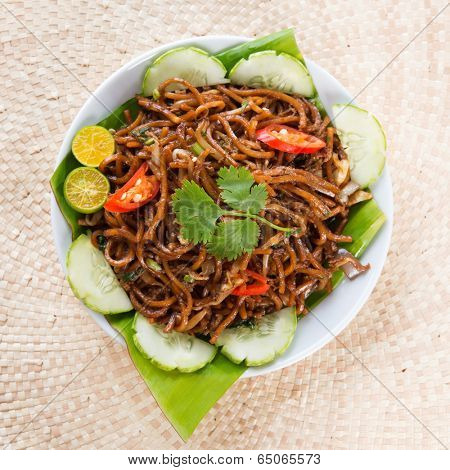 Asian food spicy fried noodles, ready to serve on dining table.