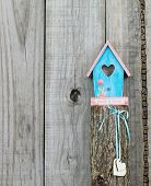 Pink and teal blue birdhouse (Friends and Family) with hearts hanging on wooden post poster