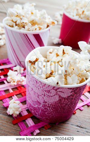 Pop corn in pink carton cups, selective focus
