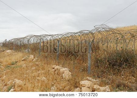 Barbed tape or razor wire fence across the desert hill on cloudy day