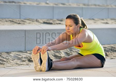 Young, pretty looking woman in sportswear, stretching and reaching her toes with her hand during an evening jog over the beach poster