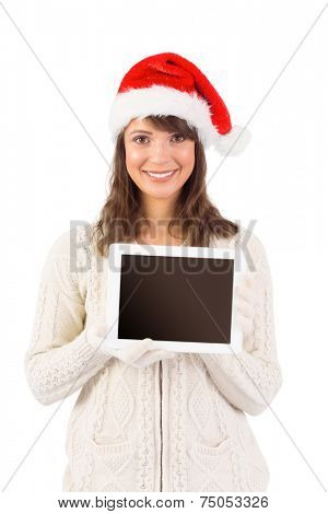 Festive brunette holding a tablet pc on white background