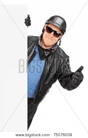 Mature biker giving thumb up behind a panel isolated on white background