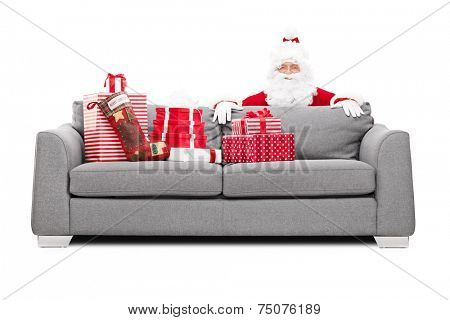 Santa Claus hiding behind a sofa full of Christmas presents isolated on white background poster