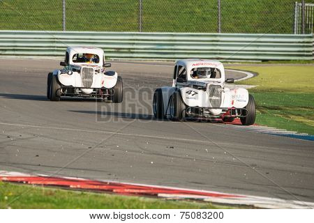 ASSEN, NETHERLANDS - OCTOBER 19, 2014: Two Legend supercars racing through a chicane on the TT Assen circuit