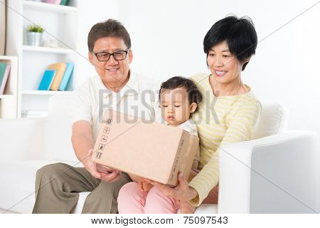 Asian family received an express courier parcel and open it at home, grandparents and grandchild living lifestyle indoor.