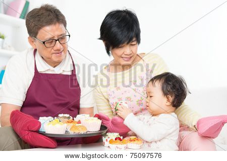 Asian family baking cake, grandparents and grandchild indoor living lifestyle at home.
