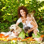 Beautiful mother and daughter relaxing in nature with pets poster