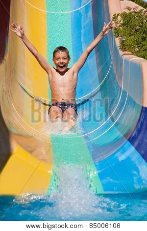 Child rolling with waterslides. Happy boy swimming