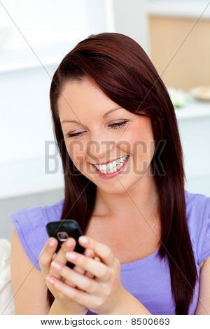 Bright Woman Texting With Her Cellphone On A Sofa
