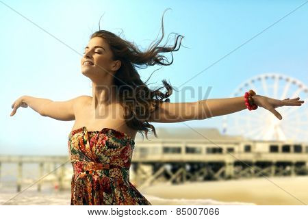 Young casual caucasian woman standing eyes closed arms wide open at summer holiday beach. Smiling, dreaming, flying, enjoying freedom. Copyspace.