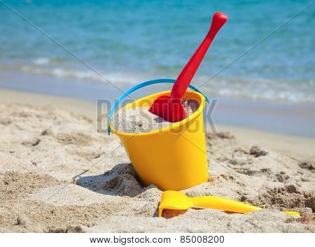 Yellow sand pail and shovel on a beach