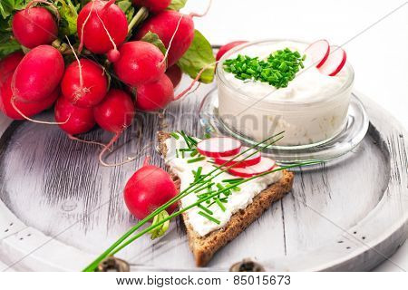 A bowl with curd and radish and a heart shaped chives decoration and brown bread
