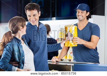 Loving expectant couple buying popcorn from male seller at concession stand in cinema