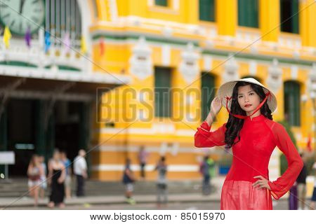 Stylish young Vietnamese woman in red standing raising her hand elegantly to her traditional hat as she stands in an urban street with colorful buildings