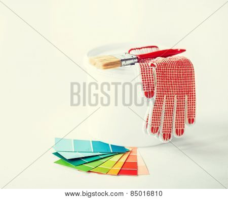 interior design and home renovation concept - paintbrush, paint pot, gloves and pantone samplers