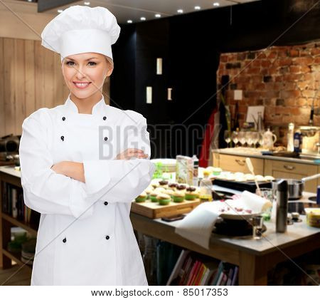 cooking, bakery, people and food concept - smiling female chef, cook or baker with crossed arms over restaurant kitchen background